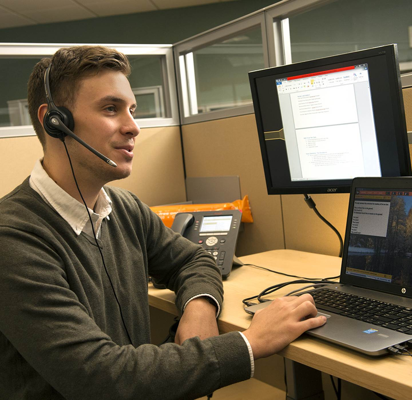 A man talking on his headset in front of the computer.