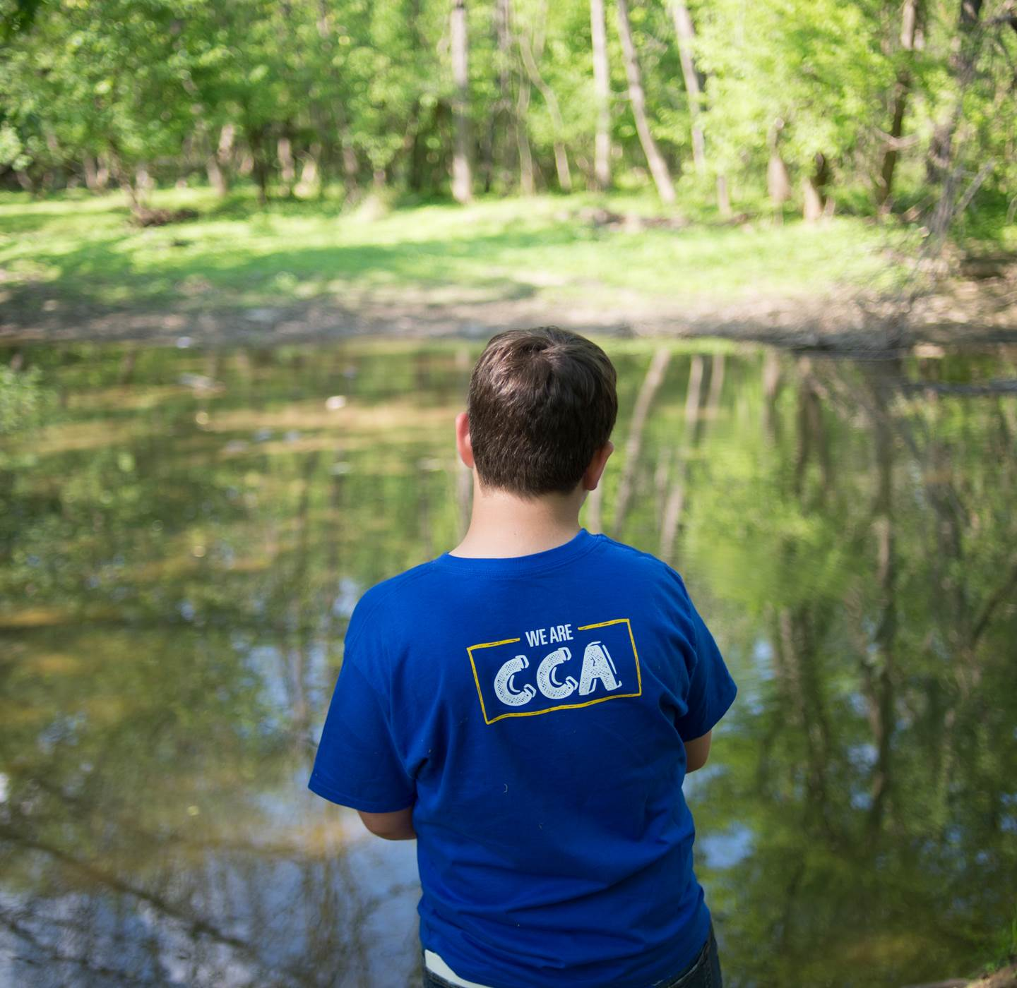 A student wearing a CCA t-shirt in front of a pond.